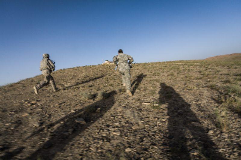 Unter Beschuss in Afghanistan: US-Soldaten versuchen, dem Kugelhagel zu entkommen. Zwischen den beiden Schatten schlägt eine Kugel ein. (c) Simon Klingert