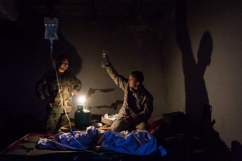 Ein amerikanischer und ein afghanischer Sanitäter versorgen auf einem kleinen Außenposten einen Jungen, der von einer Sprengfalle verletzt wurde. (c) Simon Klingert