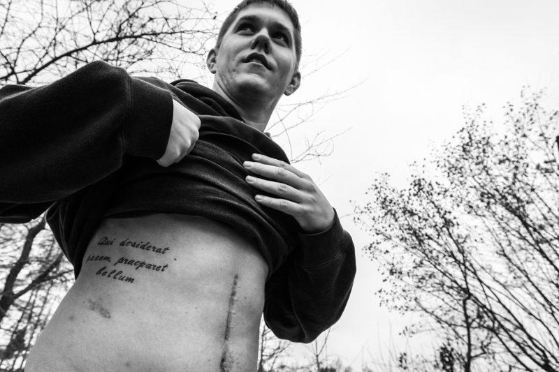 """Soldat, der im Irak-Einsatz von einem Heckenschützen verwundet wurde. """"Wer den Frieden will, bereite sich auf den Krieg vor"""" steht über seiner Hüfte tätowiert. (c) Simon Klingert"""